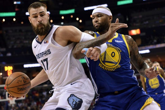 Memphis Grizzlies center Jonas Valanciunas (17) handles the ball against Golden State Warriors center DeMarcus Cousins (0) during the first half an NBA basketball game Wednesday, March 27, 2019, in Memphis, Tenn. (AP Photo/Brandon Dill)