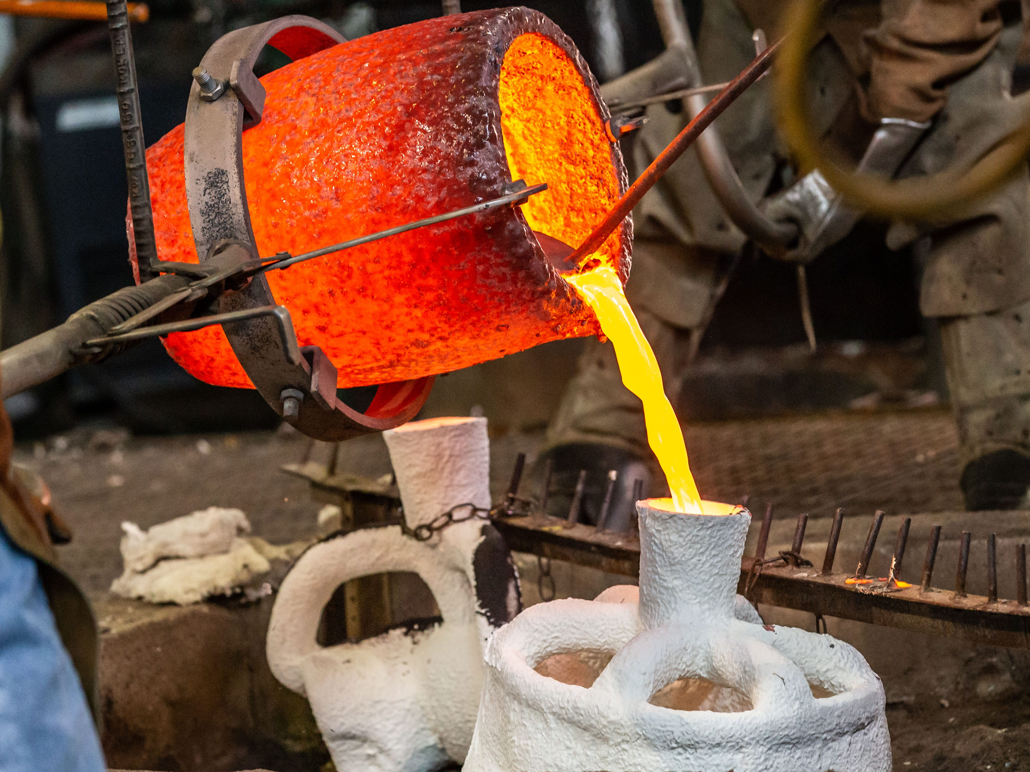 """Metal workers at Vanguard Sculpture Services in Milwaukee pour molten bronze into pre-heated mold shells as they create components of """"Da Crusher"""" bronze statue on Wednesday, March 27, 2019."""