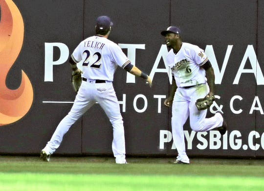 Brewers centerfielder Lorenzo Cain  is congratulated by Christian Yelich after he made a leaping catch for the final out Thursday at Miller Park.