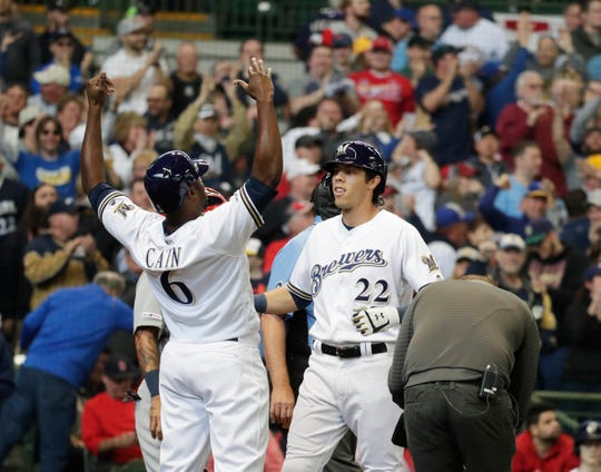 Milwaukee Brewers right fielder Christian Yelich (22) hits a three run homer in the third inning and celebrates with Milwaukee Brewers center fielder Lorenzo Cain (6) during the Milwaukee Brewers vs. St. Louis Cardinals in the MLB game at Miller Park in Milwaukee, Wisconsin, Thursday, March 28, 2019.   Rick Wood/Milwaukee Journal Sentinel