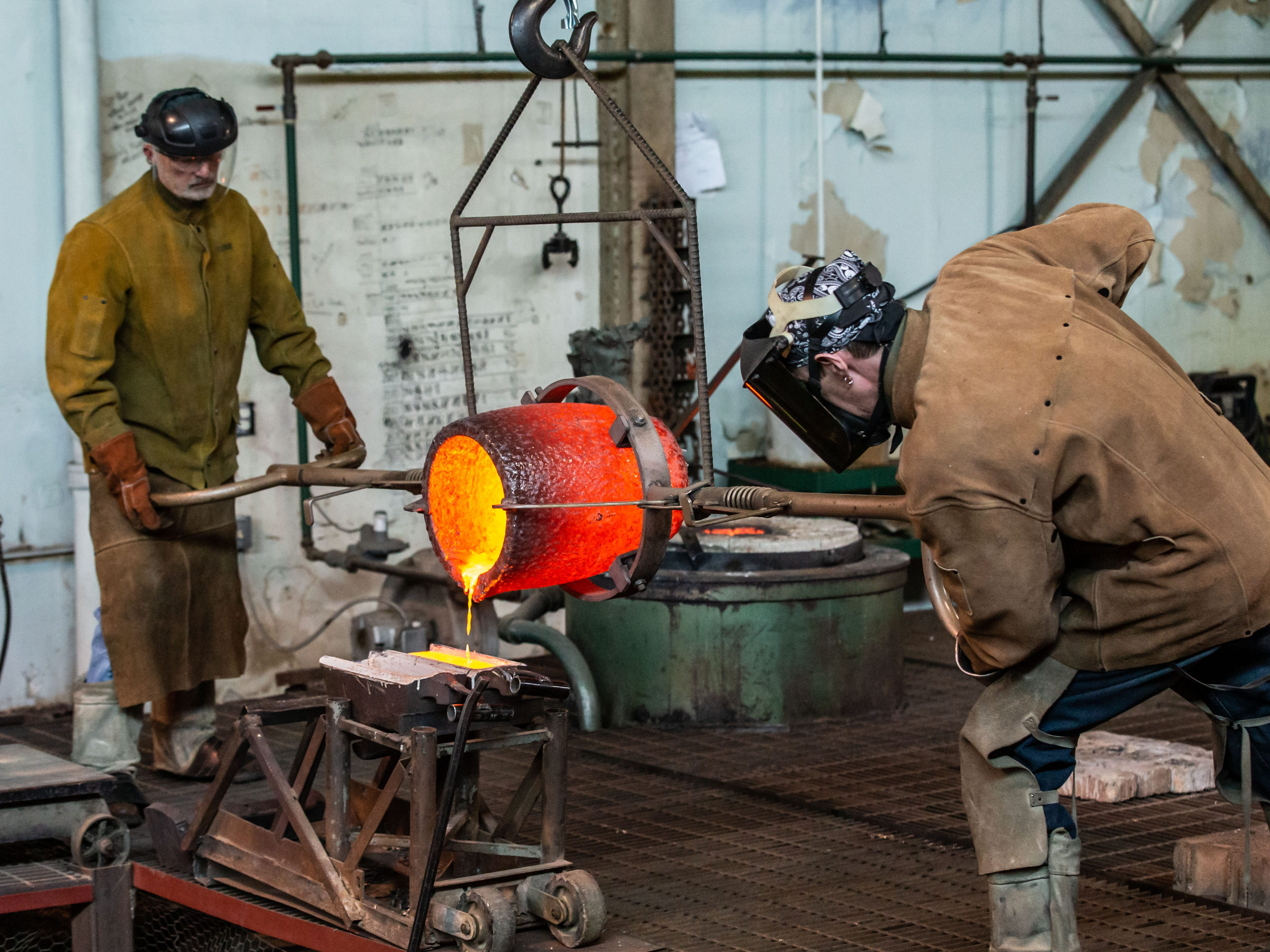 """Metal workers at Vanguard Sculpture Services in Milwaukee pour out excess molten bronze after completing several components of """"Da Crusher"""" bronze statue on Wednesday, March 27, 2019."""