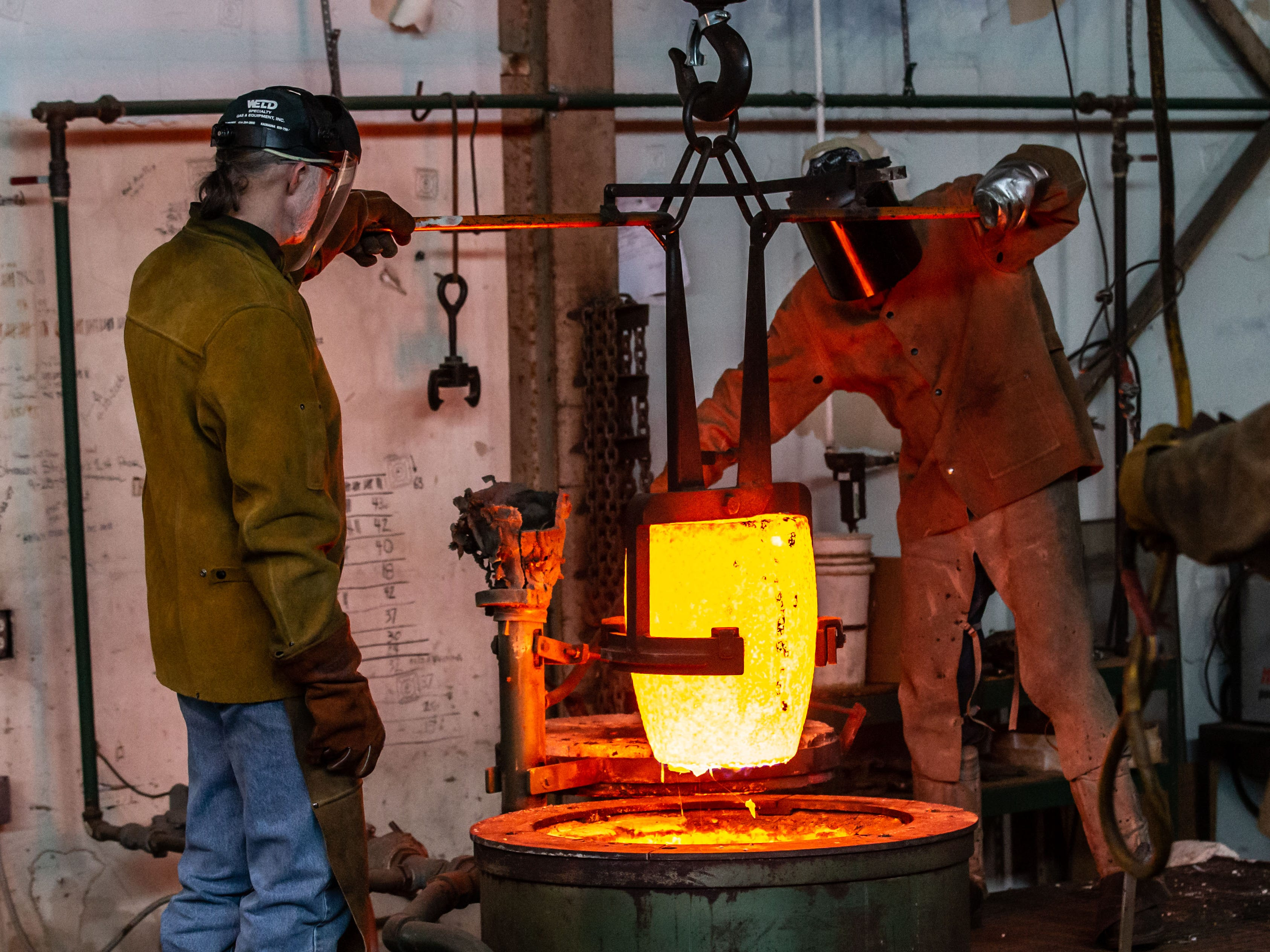 """Metal workers at Vanguard Sculpture Services in Milwaukee handle a crucible of molten bronze while pouring components of """"Da Crusher"""" bronze statue on Wednesday, March 27, 2019."""