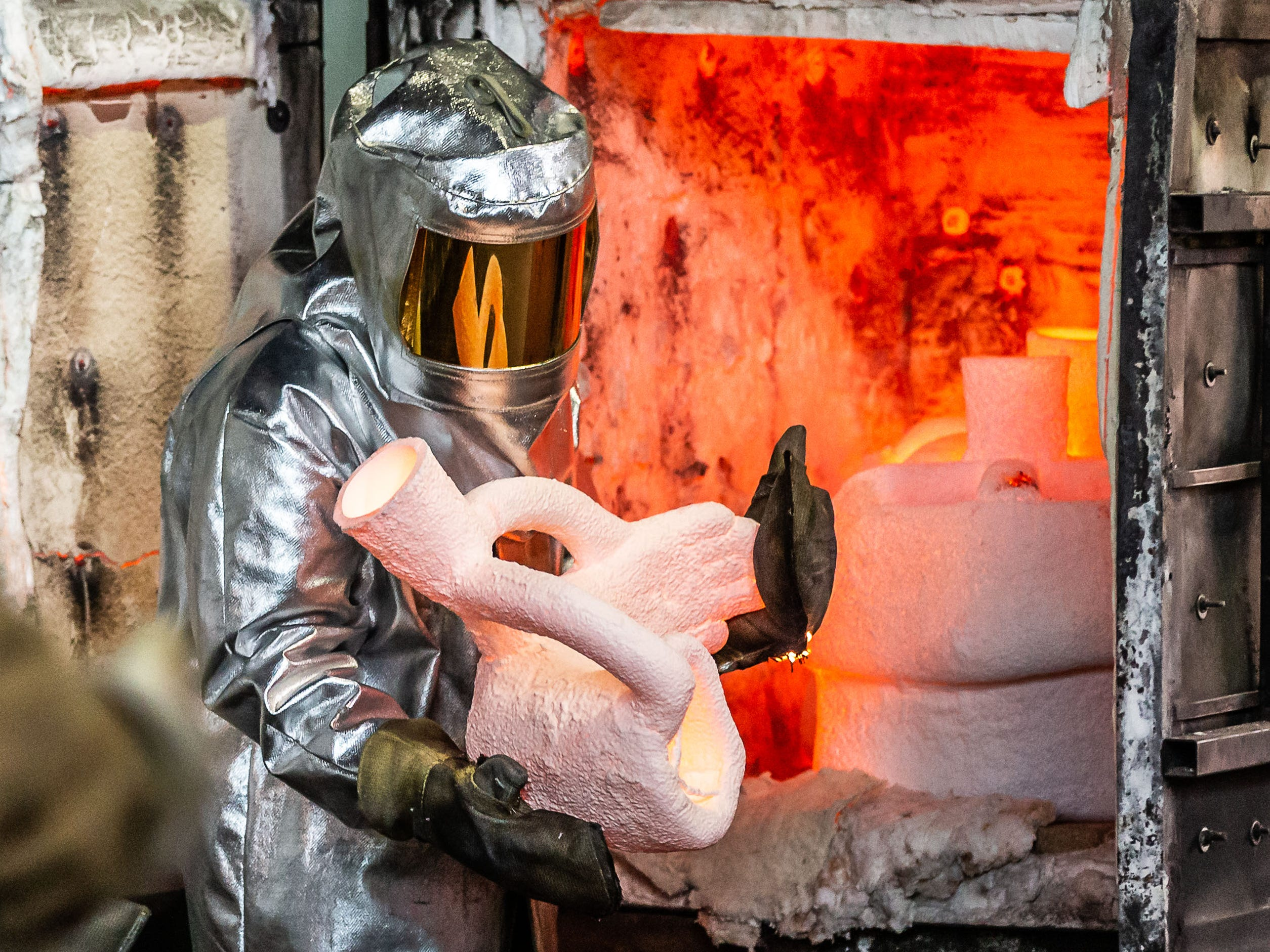 """A metal worker at Vanguard Sculpture Services in Milwaukee removes pre-heated mold shells from a kiln prior to pouring components of """"Da Crusher"""" bronze statue on Wednesday, March 27, 2019."""
