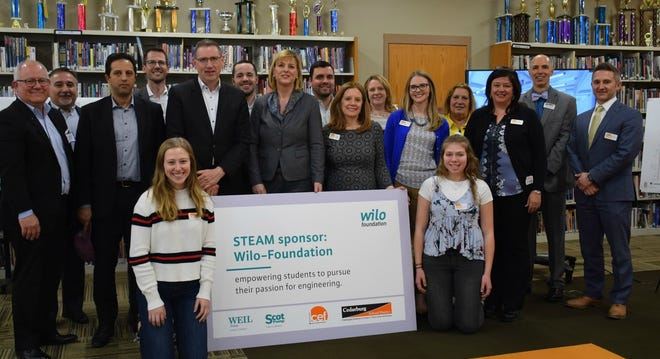 Members of Wilo Co. and Cedarburg Education Foundation (CEF) members pose for a picture during a ceremony celebrating the company's $100,000 donation to the district's STEAM efforts. Pictured are (from left, back row) Dave Wilkerson of Wilo USA-Scot Pump, Jeff Plaster of Wilo USA-Weil Pump, Mahmud Al-Haj Mustafa of Wilo SE, Daniel Podgorny of Wilo USA, Georg Weber of Wilo SE, Tim Kowaleski of Wilo USA-Weil Pump, Evi Hoch of the Wilo Foundation, CEF Board members Marc Martino, Angela Lubben, Stacy Wilke, Brooke Napiwocki, Barb Tenpenny, CEF President Julie Cosich, Cedarburg Schools Superintendent Todd Bugnacki, CEF Board member Mark Repenshek, (front) CEF student ambassadors Kyra Schachenman and Josslyne Kunz.