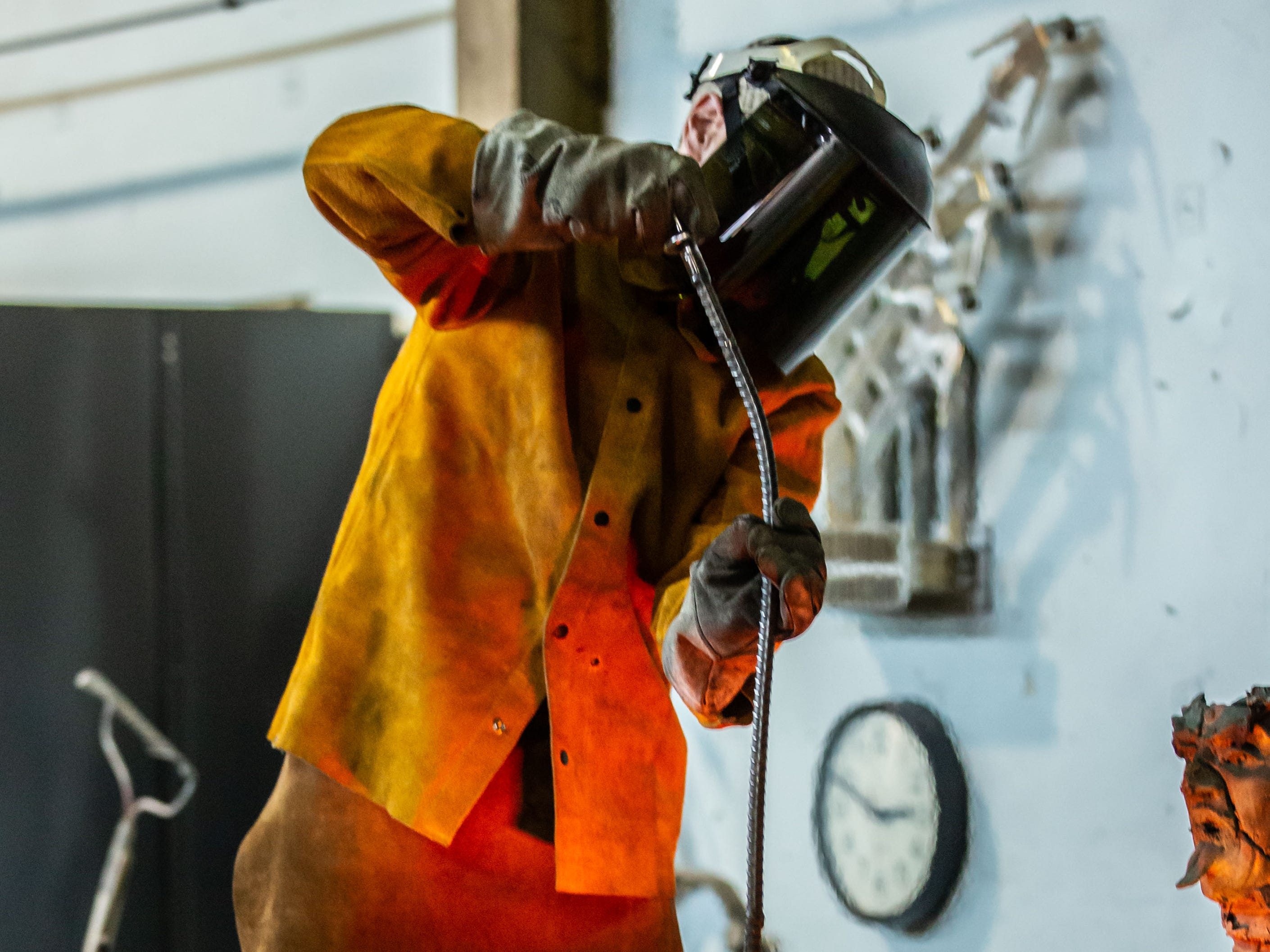 """A metal worker at Vanguard Sculpture Services in Milwaukee removes impurities from a crucible of molten bronze prior to pouring components of """"Da Crusher"""" bronze statue on Wednesday, March 27, 2019."""