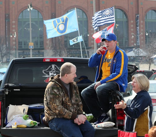 Glen Ross (from left) of Racine, Ryan Smoot of Pewaukee and Laree Allen of Fort Atkinson enjoy the warmer weather while tailgating on a tailgate before the game.