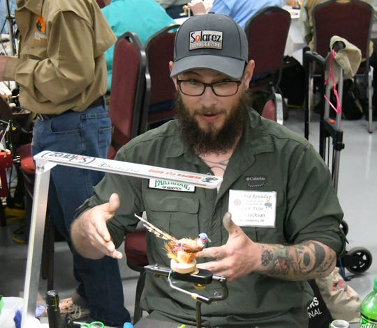 Joe Jackson talks about the fly fishing-inspired pheasant sitting on top of his vice clamp Thursday afternoon at the Sowbug Roundup. The Indianapolis resident has been making ties for about three-and-a-half years.