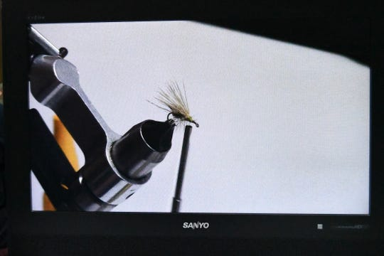 One of Ralph Rhoades' completed flies is seen under magnification on a video screen Thursday at the 22nd annual Sowbug Roundup.