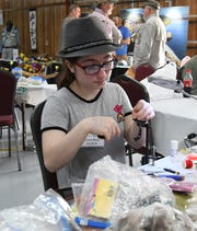 Grace Reed of Gassville begins crafting a fly Thursday at the 22nd annual Sowbug Roundup.