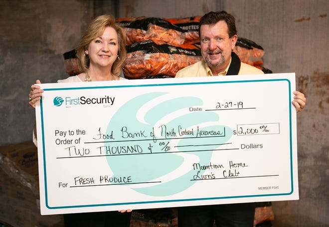Shirley Clark (left), Food Bank of North Central Arkansas Program Director, accepts a $2,000 donation fromGeorge Truell of theMountain Home Lion's Club. The donation will be used for the Food Bank's Produce and Health Foods Initiative.