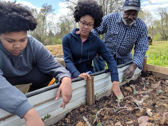 (From left to right): Ayden Gibson, A'Shiree Gibson, and Geiger community garden manager Jimmy Williams examine garden beds ahead of spring planting on March 26, 2019.