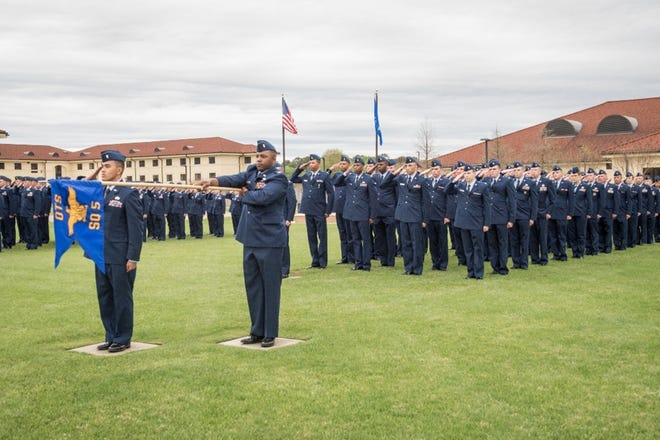 "Air Force Officer Training School officer trainees salute during the ceremonial playing of ""Ruffles and Flourishes,"" March 15, 2019, Maxwell Air Force Base, Alabama. This graduating class of officers is the largest ever and one of the first under the new consolidated OTS training program."
