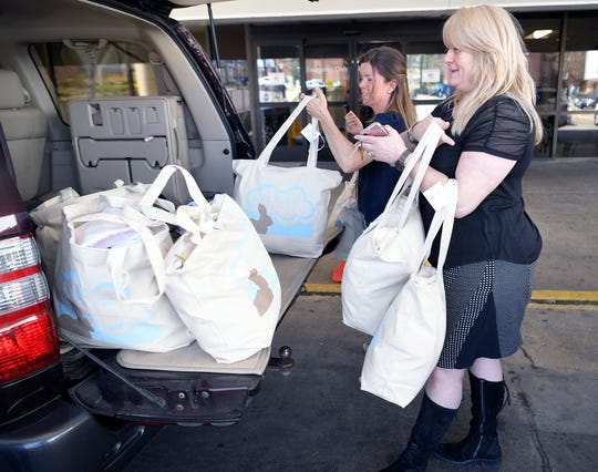 Lena Levendoski, center, drops off bags of clothing and blankets for newborns in need at Nashville General Hospital on Wednesday, March 28, 2019.  Kate Haygood, volunteer coordinator at Nashville General, helps Levendoski carrying in donations.  Levendoski started a non-profit,, Strick's Gift, that collects infant clothes to give to some of these newborns in need as a way to give them hope and tokeep the memory of her son alive.
