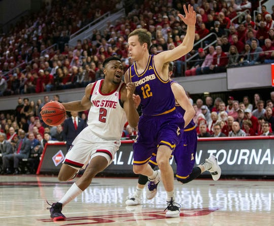 North Carolina State's Torin Dorn (2) dribbles past Lipscomb's Matt Rose (12) during the first half of the quarterfinals of the NIT on Wednesday, March 27, 2019, in Raleigh, N.C. (Travis Long/The News & Observer via AP)