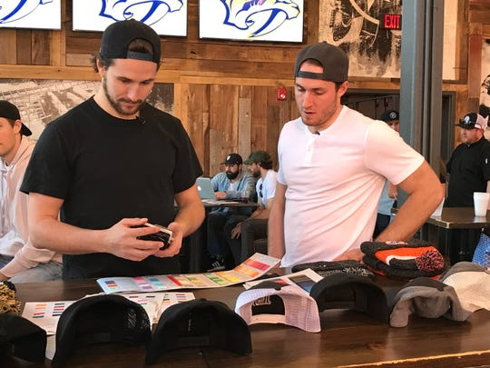 Predators' Filip Forsberg (left) and Colton Sissons designed team hats on Wednesday at Dierks Bentley's Whiskey Row as part of an event hosted by the brand '47.