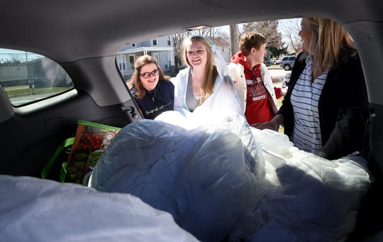 OSU-Newark social work students Mary Dow, Ashley Moriarty, Connie McDaniel, and Kim Novak unload towels, donated from Cherry Valley Lodge, to give to Vertical 196 in Newark on Tuesday, March 26, 2019. The group of graduating seniors gathered two carloads of donations of tents, tarps, towels, clothing, and other personal and household items for the homeless outreach center.