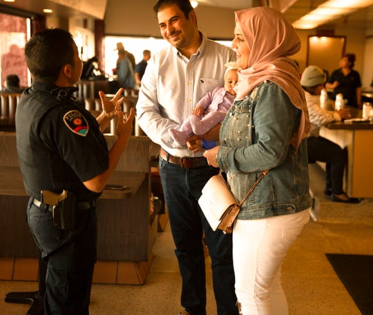 Las Cruces Police Officer Lt. Kiri Daines talks with Ayat Bataineh, Amer Al-Radaideh and four-month old Karima Al-Radaideh at Old Town Restaurant Thursday during Coffee with a Cop.