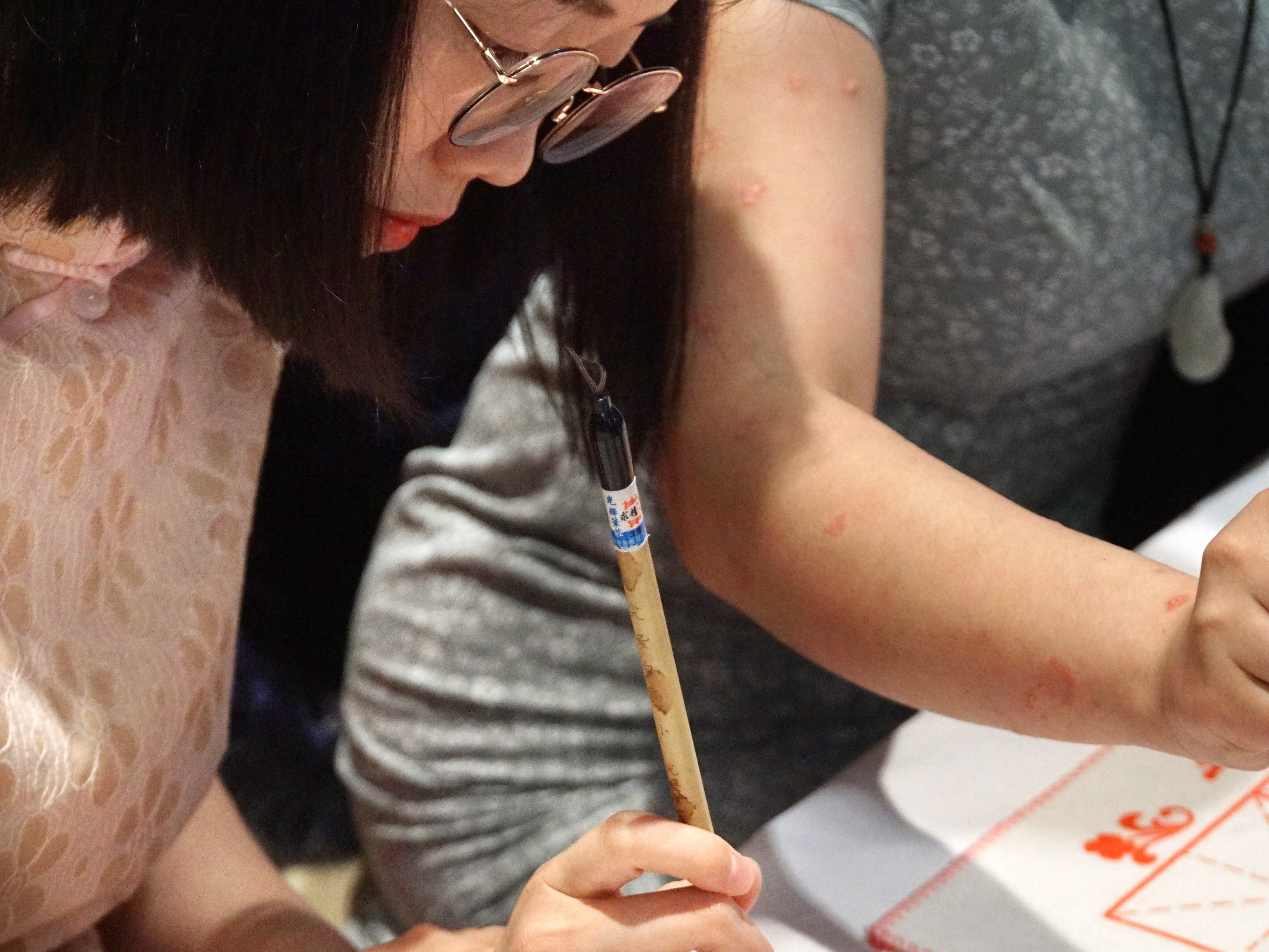 Danhua Ren writes an English name in Chinese characters during the fair.