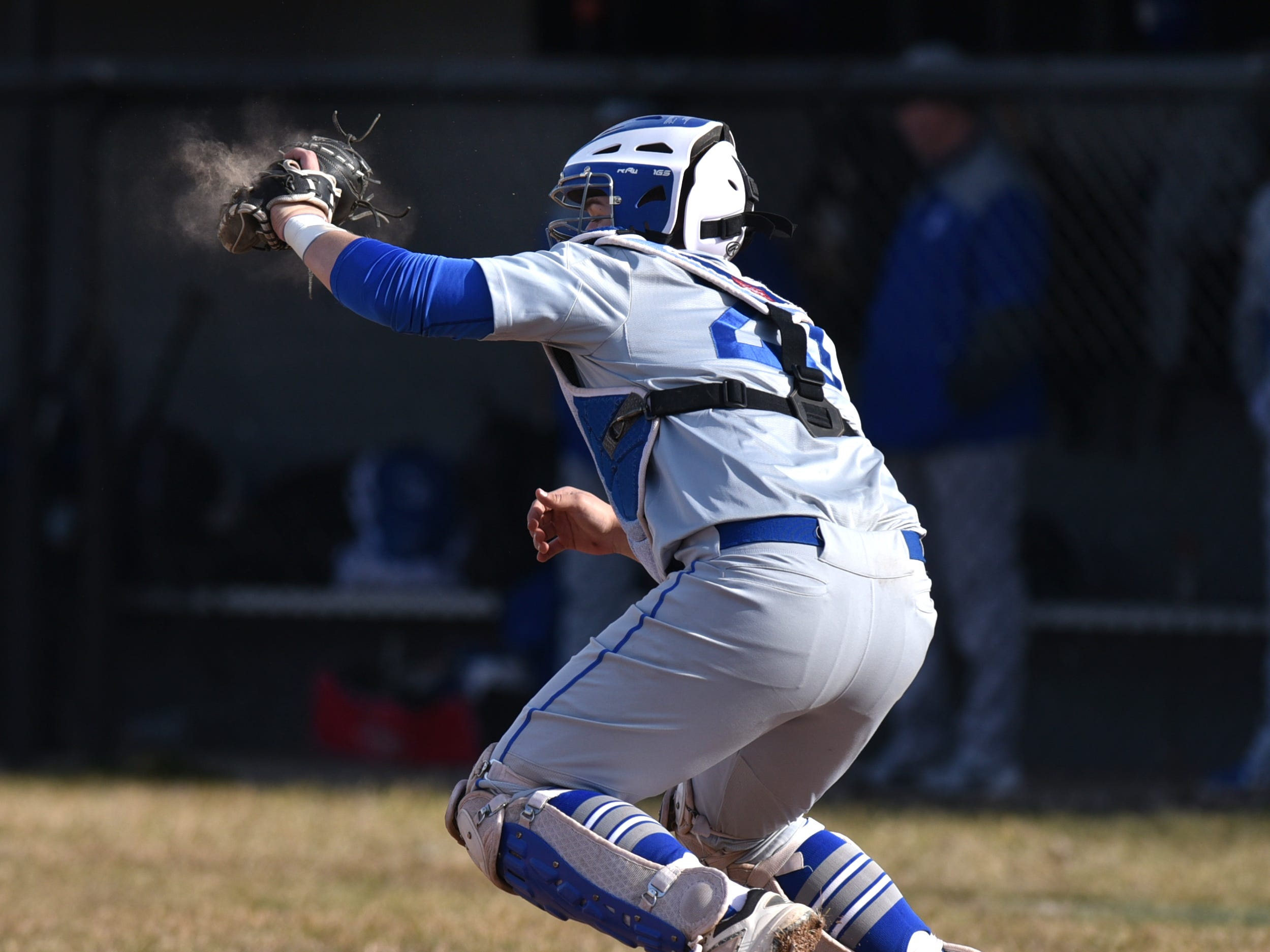 Salem High catcher Tyler Overaitis snaps a pitch into his glove as a small cloud of dust appears.