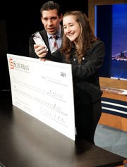 """Sydni Rotenberg Facetimes with her award-winning collaborator Michael Soverinksy (who was in Florida at the time) after the pair won a $1,500 from the Suburban Collection on March 28 for their anti-distracted driving video """"Focus on the Road"""". At left is Suburban Collection Social Media representative Dan Fuoco.  Rotenberg and Soverinksy are North Farmington High students."""