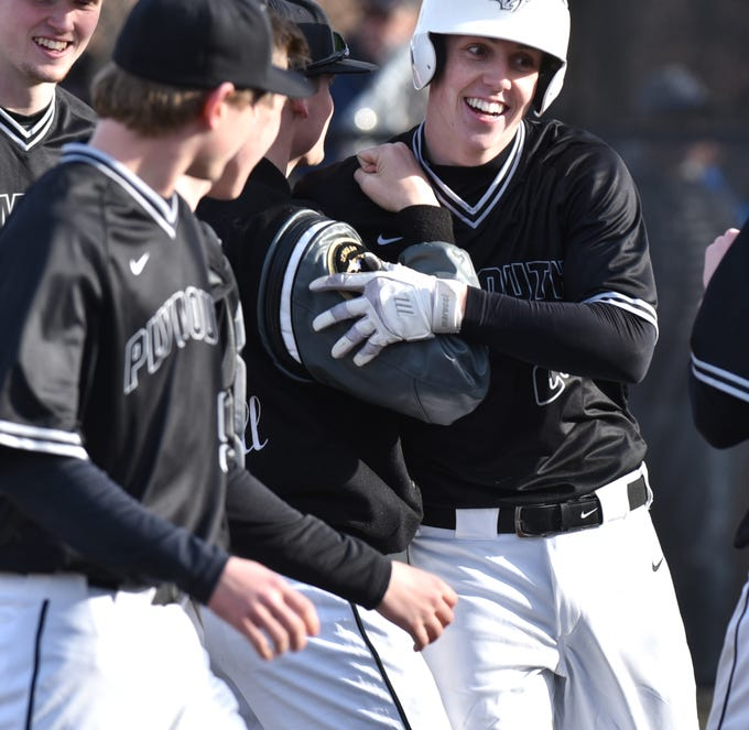 Plymouth's Alec Beshears is greeted a home plate by his teammates after hitting a home run against Salem High.