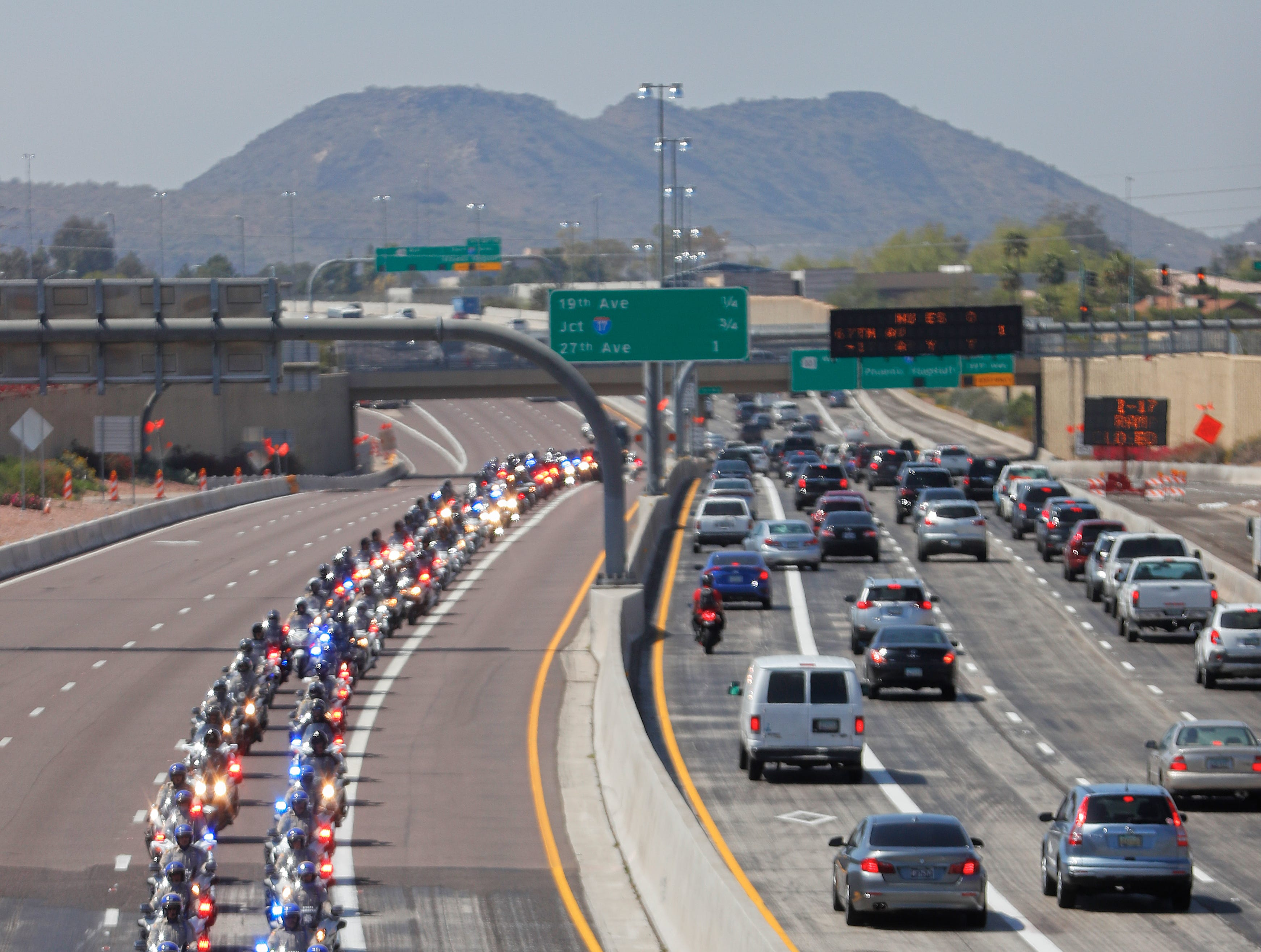 The funeral procession for Phoenix Officer Paul Rutherford drives east on Loop 101 in Phoenix on March 28, 2019.