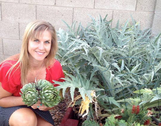 Barbara Ruhs holds artichokes in her garden at her north Phoenix home in June 2016. She regularly checks out seeds for her garden from the Phoenix Library Seed Library.