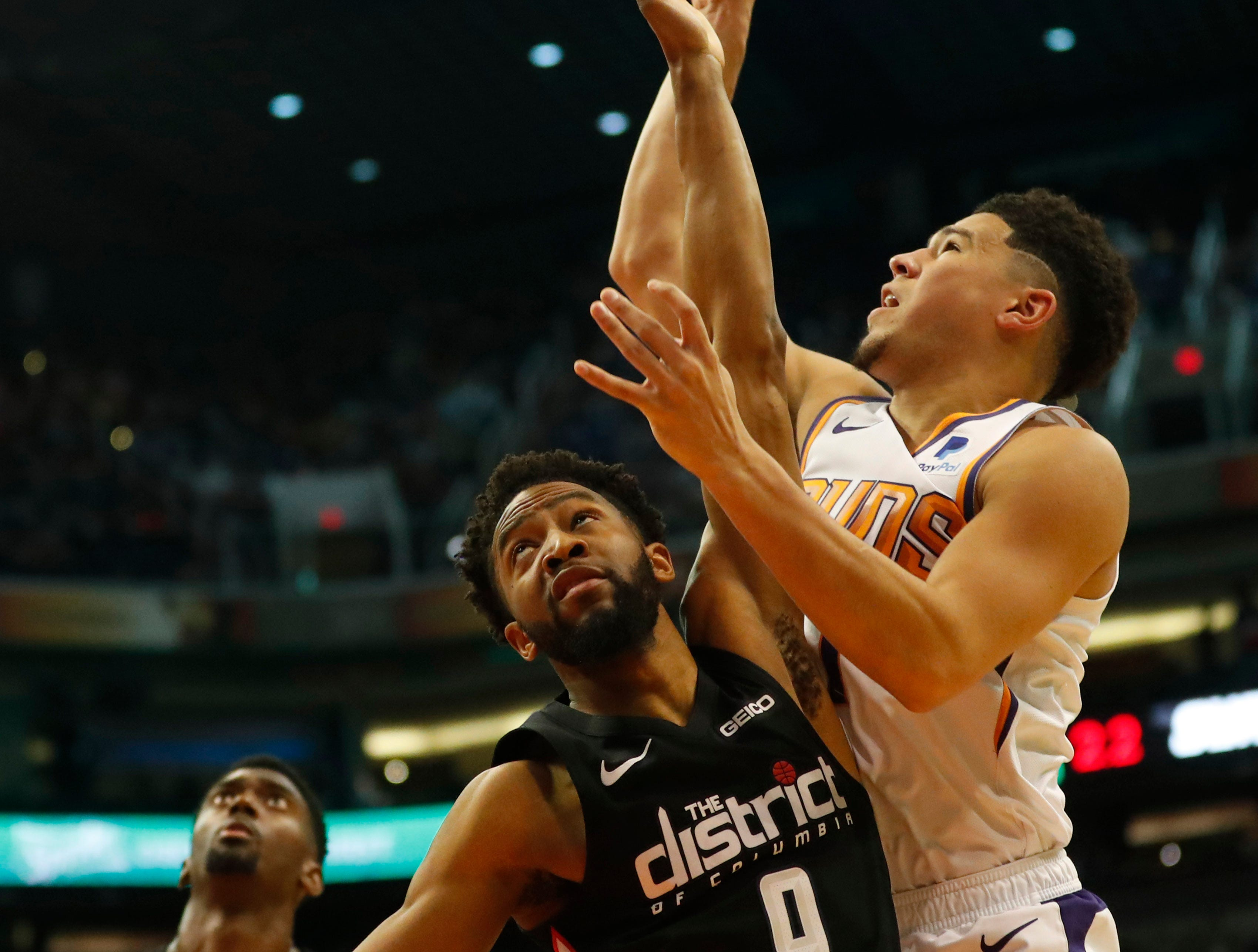 Phoenix Suns guard Devin Booker (1) watches his shot while defended by Washington Wizards guard Chasson Randle (9) during the first quarter in Phoenix March 27, 2019.