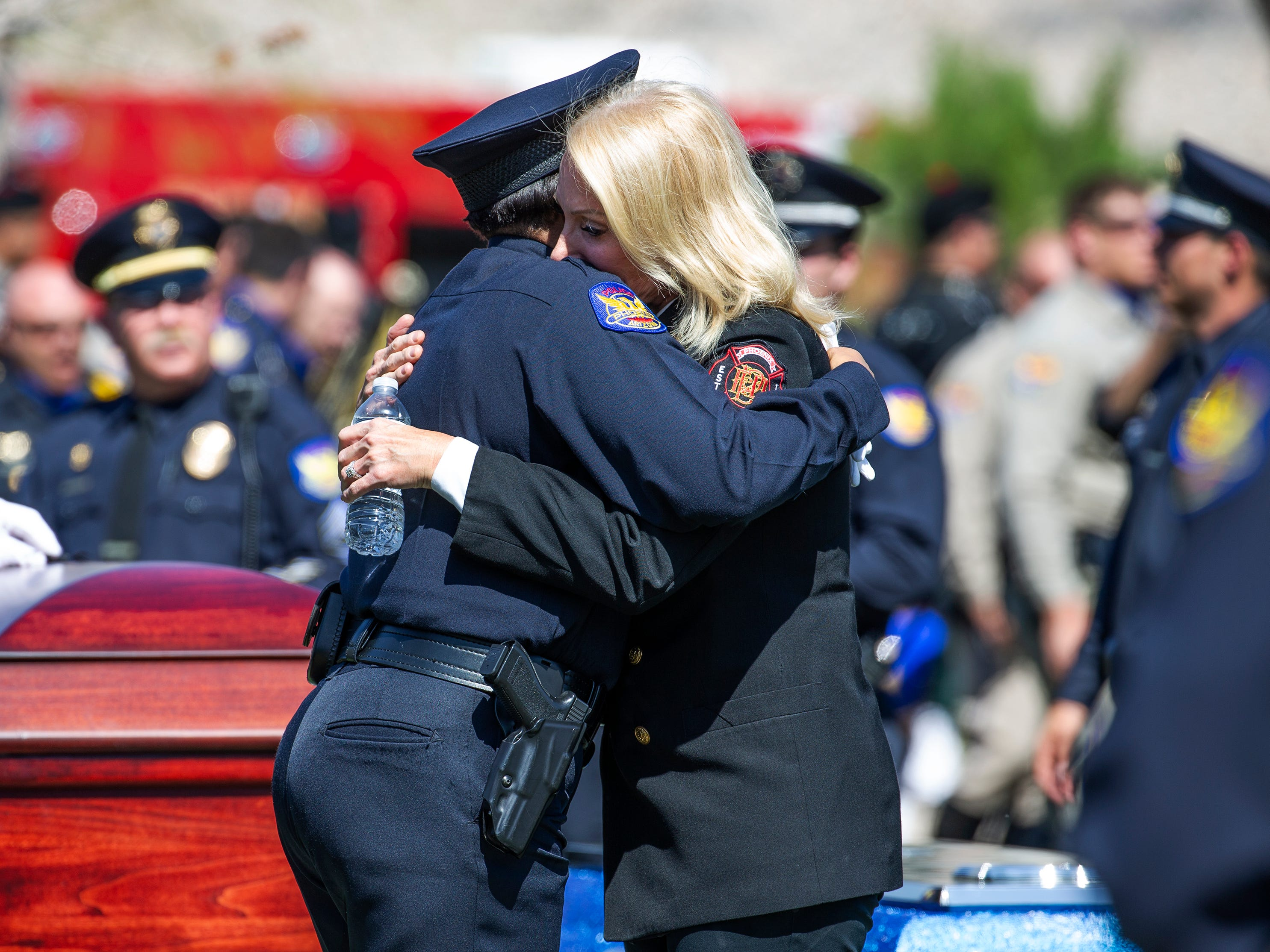Phoenix Police Chief Jeri Williams (left) is hugged by Phoenix Fire Chief Kara Kalkbrenner after graveside services for Phoenix police Officer Paul Rutherford at Phoenix Memorial Cemetery March 28, 2019. Rutherford was killed while investigating the scene of an auto accident in Phoenix.