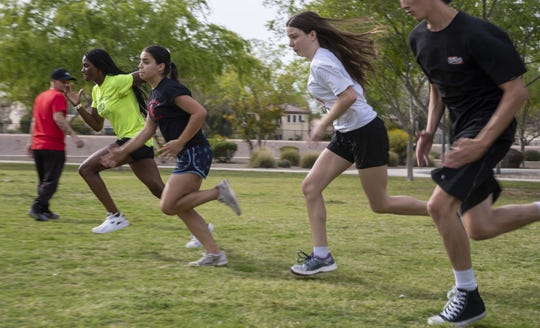 Leading Edge Academy coach Ryan Johnston is working with students, Daijanae Sample, on far left and Jordyn Espinoza, during their track and field at Tibshraeny Family Park, in Chandler, Az. Leading Edge Academy has no track.  A team has to walk nearly a mile to get to his park for practice.