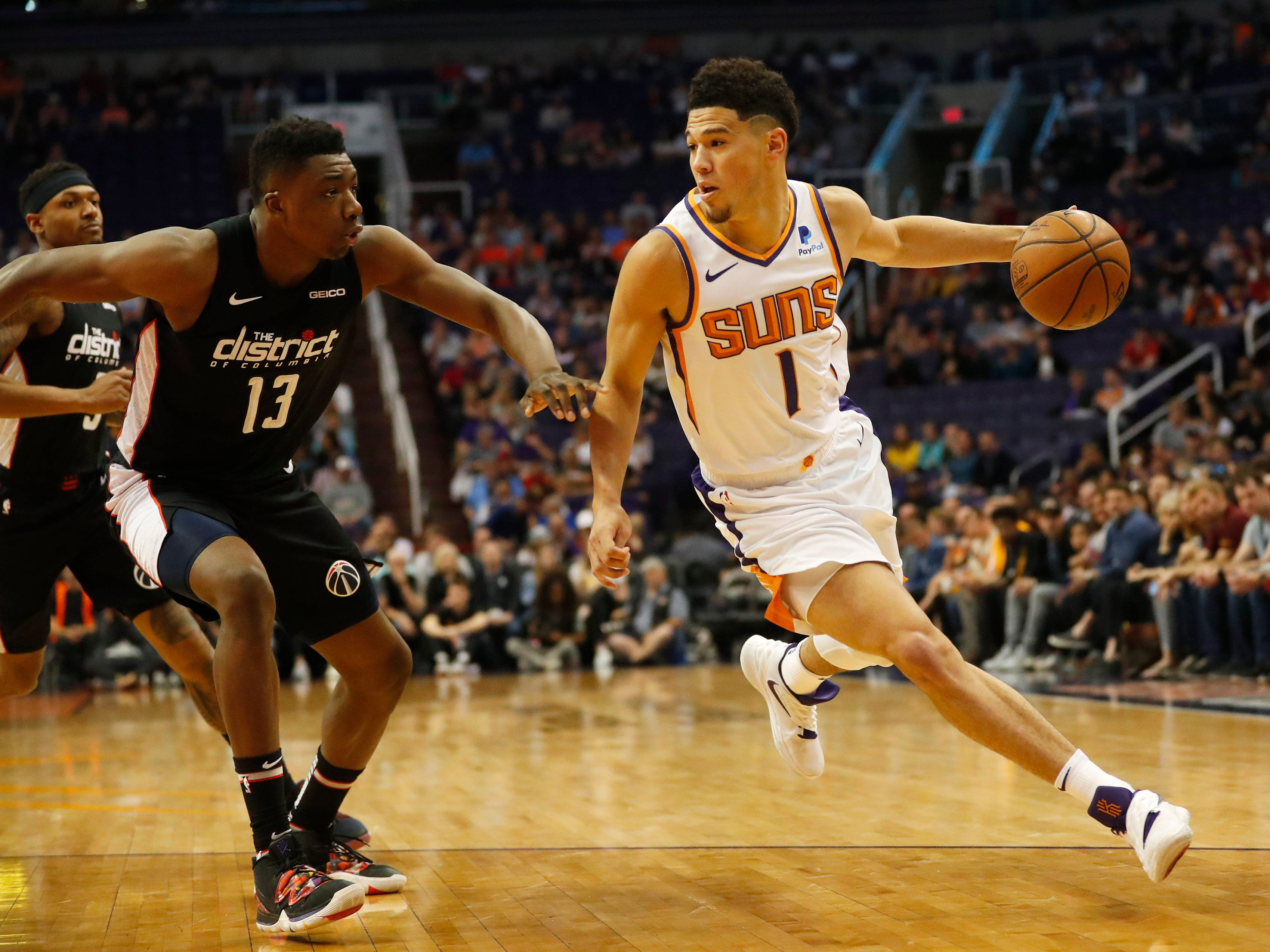 Phoenix Suns guard Devin Booker (1) is defended by Washington Wizards center Thomas Bryant (13) during the first quarter in Phoenix March 27, 2019.