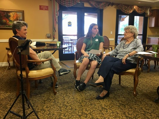 Carla Cotton, a teacher at All-Saints' Episcopal Day School in Phoenix, listens in on Meredith Scott's interview with her great-grandmother Carolyn Scott.