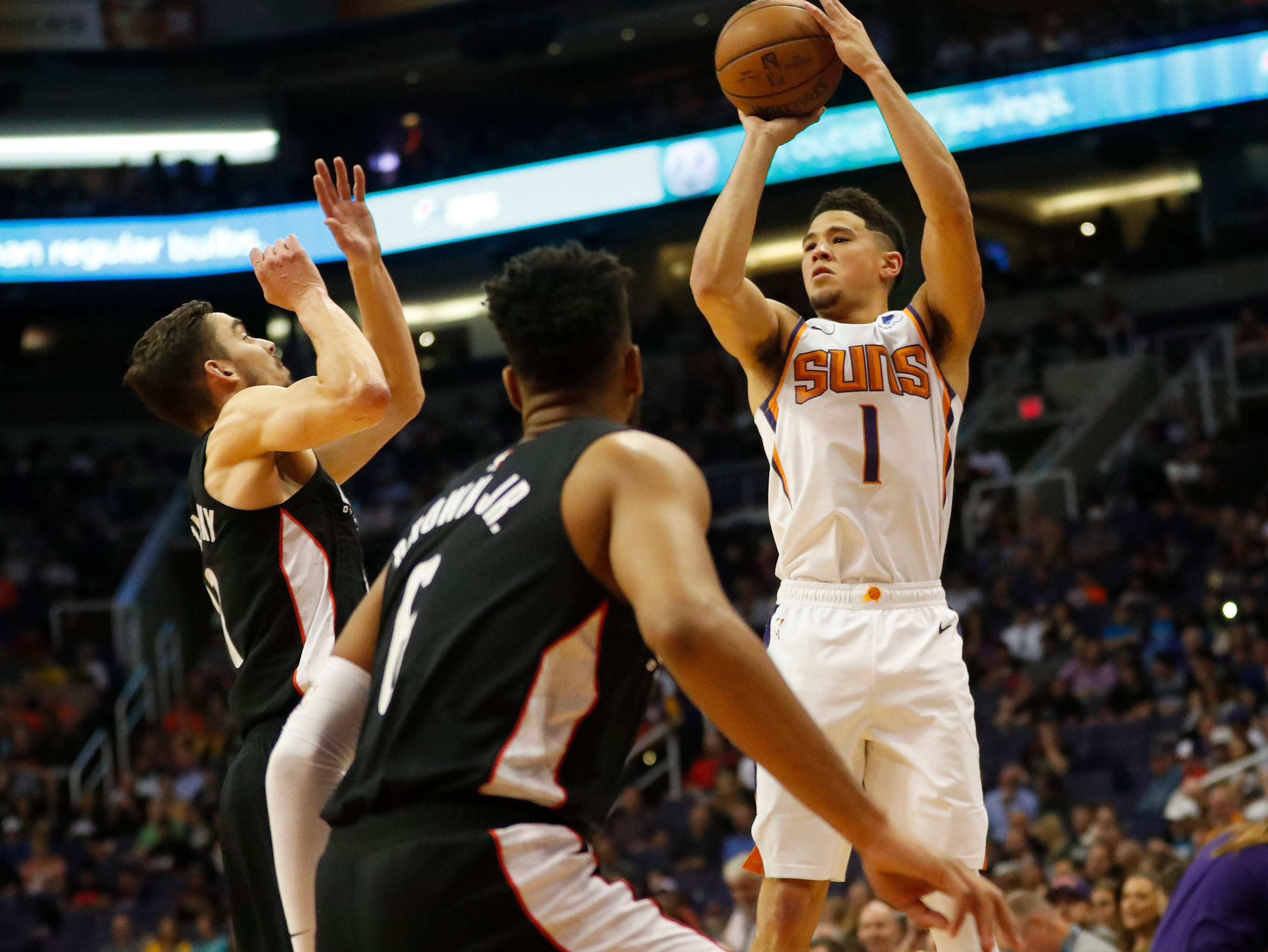 Phoenix Suns guard Devin Booker (1) attempts a three-point shot against the Washington Wizards during the first quarter in Phoenix March 27, 2019.