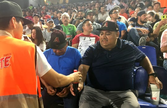 """Rogelio Moran (left), 62, and Juan Pintor, 40, flew from Tampico to Monterrey, Mexico, to watch two spring-training games between the Arizona Diamondbacks and the Colorado Rockies. The two said they became Diamondbacks fans because they like the players. When asked which ones, Moran paused and then said, """"All of them."""""""