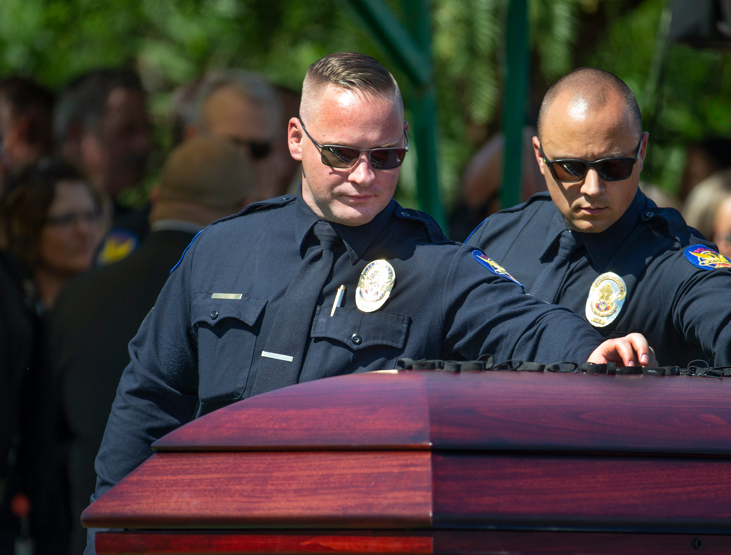 Phoenix police officers place badges atop the casket of Phoenix police Officer Paul Rutherford after graveside services at Phoenix Memorial Cemetery March 28, 2019. Rutherford was killed while investigating the scene of an auto accident in Phoenix.