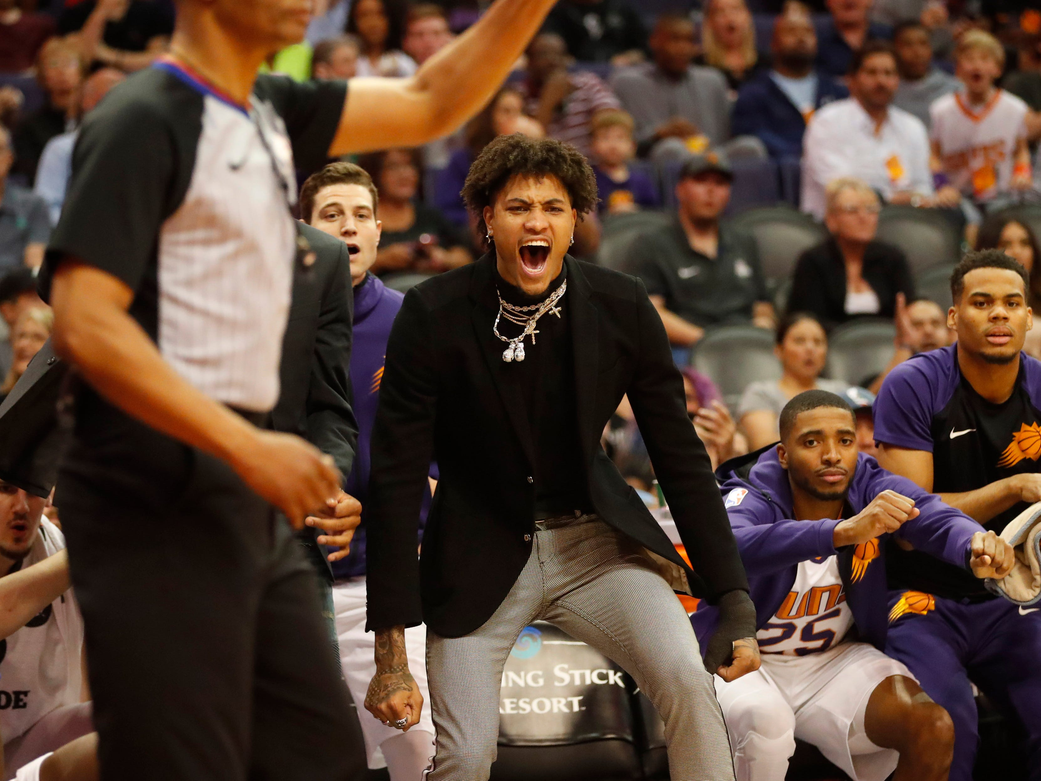 Phoenix Suns injured forward Kelly Oubre Jr. cheers for his team during the first quarter against the Washington Wizards in Phoenix March 27, 2019.