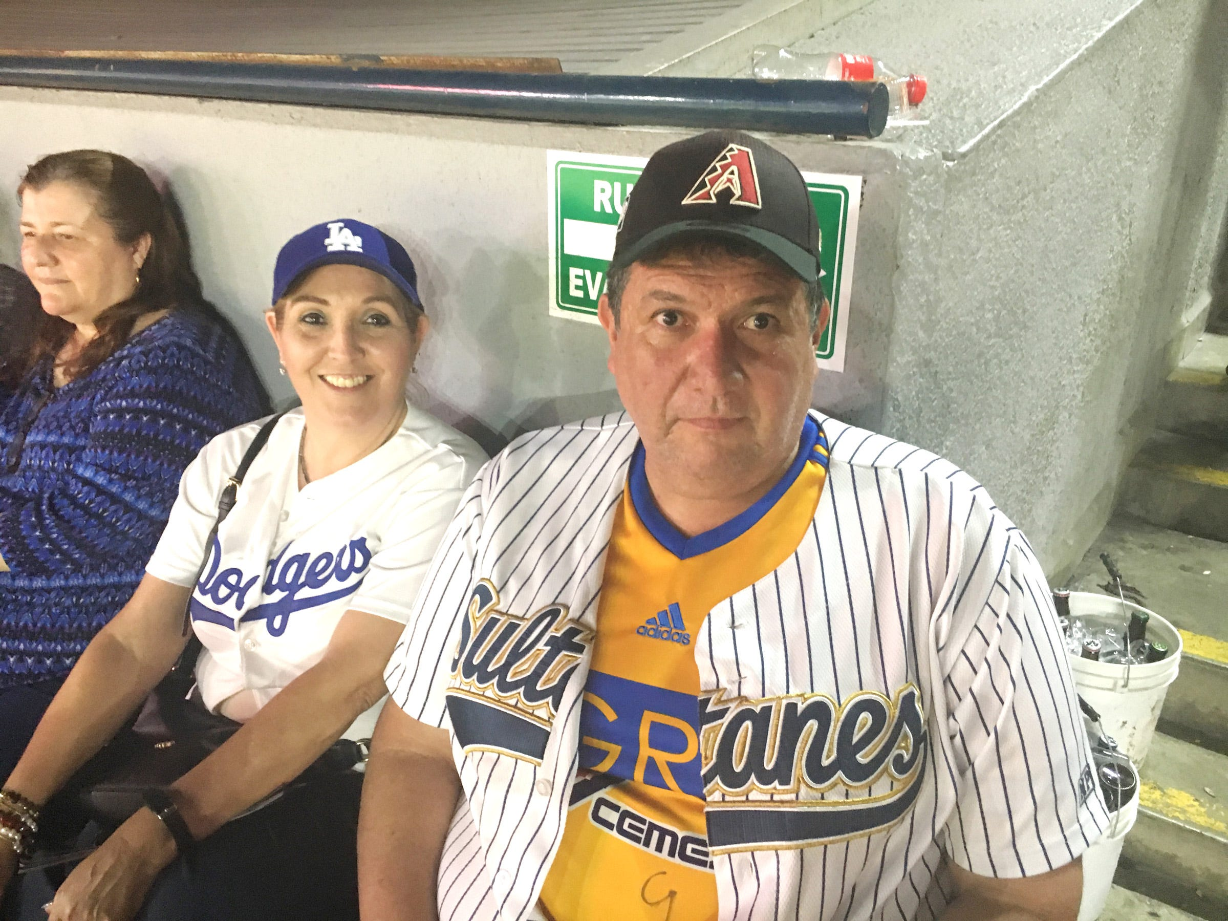 These two baseball fans wore jerseys and caps showing their support for the Arizona Diamondbacks, the Los Angeles Dodgers and the Sultanes de Monterrey, Mexico.