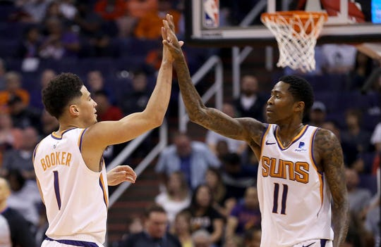 Phoenix Suns guard Devin Booker (1) celebrates his dunk against the Washington Wizards with guard Jamal Crawford (11) during the first half of an NBA basketball game Wednesday, March 27, 2019, in Phoenix. (AP Photo/Ross D. Franklin)