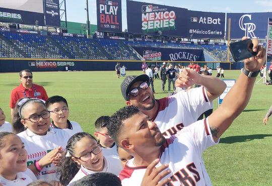 Arizona Diamondbacks third baseman Eduardo Escobar poses for a photo with outfielder David Peralta and children inside a baseball stadium in Monterrey, Mexico, during an event to introduce kids in Mexico to baseball.