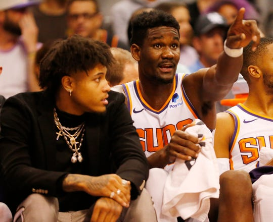 Phoenix Suns center Deandre Ayton (22) talks with injured forward Phoenix Suns forward Kelly Oubre Jr. (left) during the first quarter against the Washington Wizards in Phoenix March 27, 2019.
