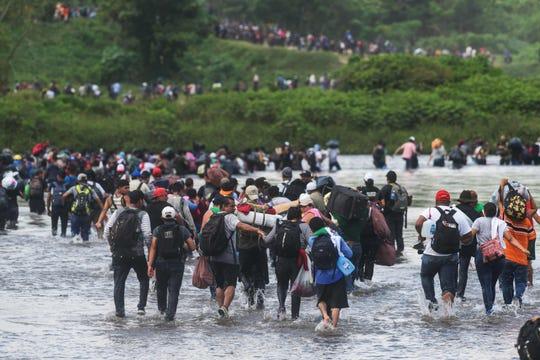 Migrantes de la caravana cruzan el río Suchiate al sur de México.