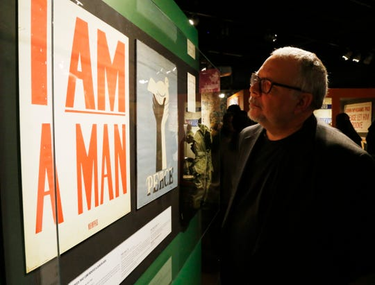 """Wade Lawrence, director of the Museum at Bethel Woods, beside a replica of an """"I Am A Man"""" placard in the exhibit, """"We Are Golden,"""" on March 28, 2019. The replica was on display as an original placard was en route to the exhibit. The original has since replaced the replica. Striking Memphis sanitation workers carried these signs in 1968."""