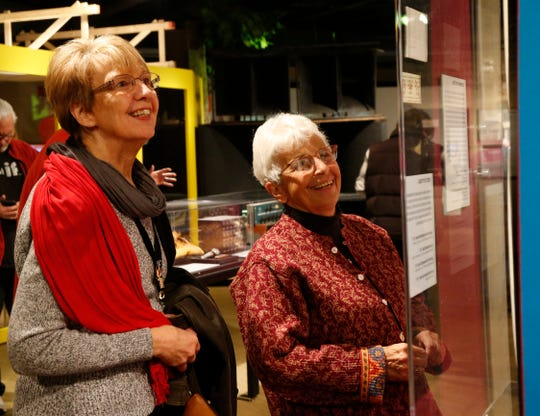 """From left, Susan Kozykowski of Barryville and Flo Mauro of Port Jervis look over artifacts from the show, """"We Are Golden"""" at Bethel Woods Center for the Arts on March 28, 2019.  Both Mauro was at the original 1969 festival."""