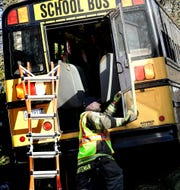 A firefighter works near an emergency door after a school bus crash at the intersection of Maryland and Belvidere avenues in York City Thursday, March 28, 2019. The bus was transporting students from the high school to the Edgar Fahs Smith STEAM Academy when it was involved in a crash. Six William Penn High School students were taken to the hospital with injuries. Bill Kalina photo