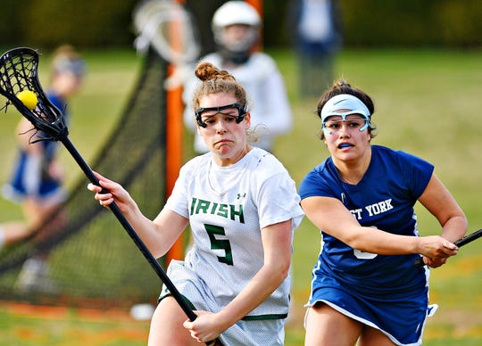 York Catholic's Grace Doyle, left, carries the ball while West York's Libby Bahoric defends during girls' lacrosse action at York Catholic High School in York City, Thursday, March 28, 2019. York Catholic would win the game 23-3. The Irish are off to a 4-0 start. Dawn J. Sagert photo