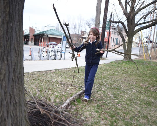 Holden Feeser, 6, picks up branches around the grassy area near an unused portion of land near the King Street intersection of the Heritage Rail Trail in York. Feeser and her mother, Meagan Give, launched a fundraising campaign to repurpose the near acre-sized lot into Pal's Dog Park.