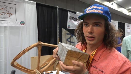 Caleb Campbell of Bend, Ore., shows off a block of salvaged white oak lumber which he and his father, Scott Campbell of Corvalis, Ore., use to make bicycle frames.