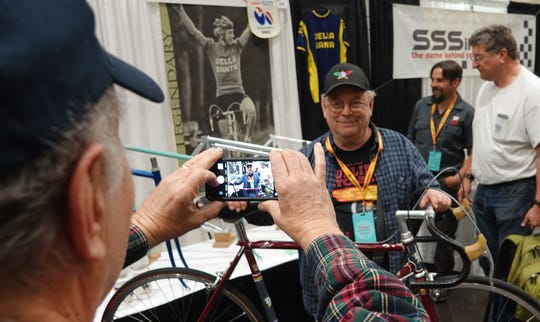 Steel bicycle frame builder Roland Della Santa of Reno, who built frames for three-time Tour de France winner Greg LeMond, poses for a photo in front of one of his frames and a photo of LeMond at the North American Handmade Bicycle Show in March in Sacramento, Calif.