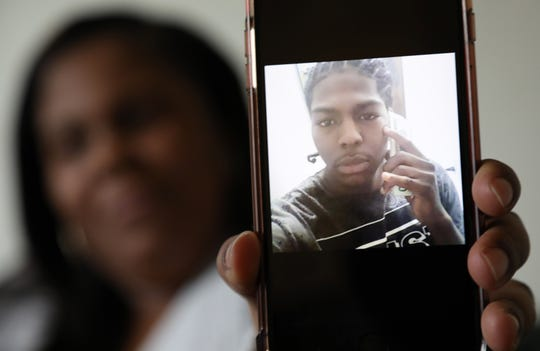 Shonday Williams holds a photo of her brother, Plush Dozier, on her cellphone. Dozier was arrested shortly after this photo was taken.