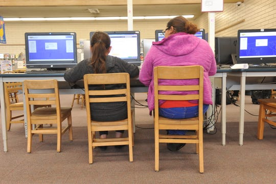 A daughter and mother work together on computers at the Steinbeck Public Library in Salinas on March 27, 2019.